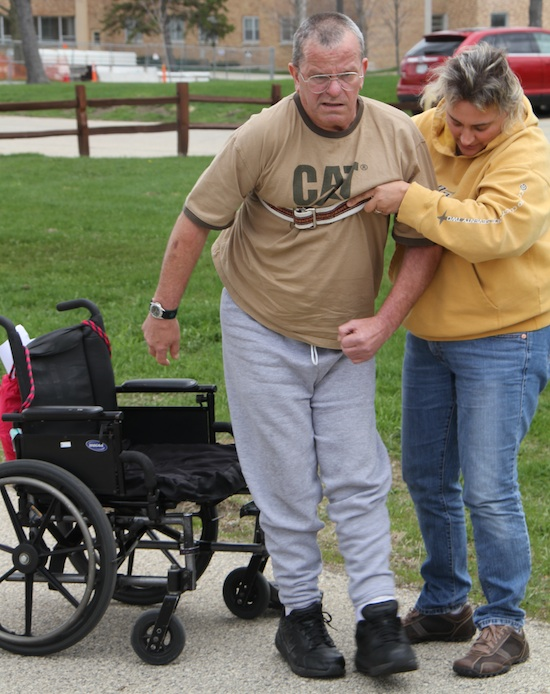 MIke's wife hangs on to the belt to help him get in and out of his wheelchair during rehabilitation from brain injury.